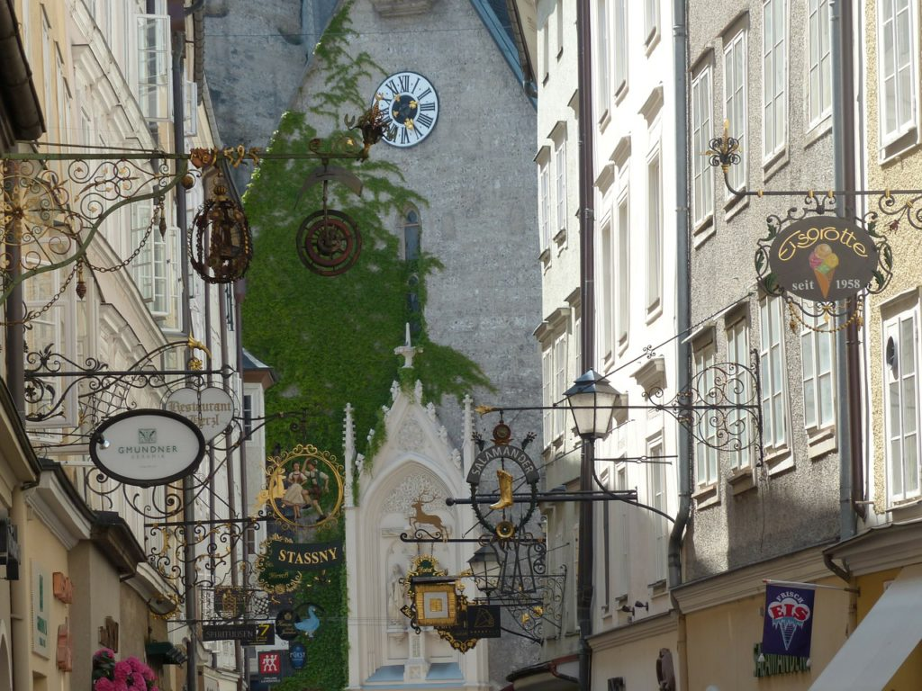 "Charming ""guild signs"" hanging from every facade in Salzburg, Austria's ""Getreidegasse"" square."